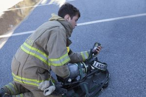 Junior Firefighter Arlan Miller checks a gauge on his new air pack. The cylinders are industry standard with 4500 psi.
